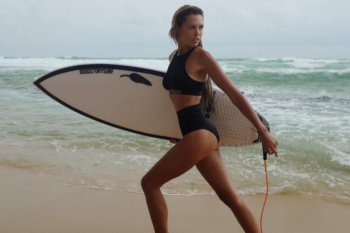 Маша Горбань с доской для серфинга на пляже
